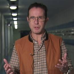 en medelåldersman som pratar och gestikulerar i en korridor