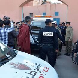 Två polisbilar och flera poliser samt fotografer.