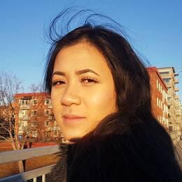Tina står på en bro med solen i ansiktet.