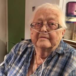 Äldre kvinna, Margon Landgren i Rossön, sitter med syrgas vid sitt köksbord