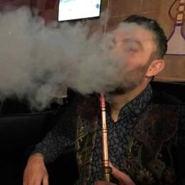 man som röker vattenpipa, stort rökmoln