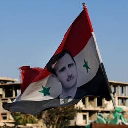 En syrisk flagg med bild på president Bashar al-Assad, i bakgrunden sönderbombade byggnader.