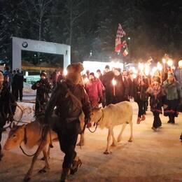 många personer som går i tåg med tända facklor, några i traditionell samisk dräkt, en man leder tre renar