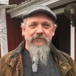 En man i grå keps och brun jacka och grått skägg står framför sitt röda hus.