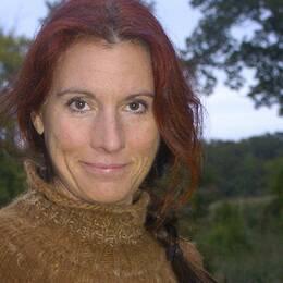 En kvinna med rött hår ler mot kameran. Delad bild. Till höger i bild två hästar i spilta.