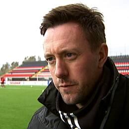 Tränaren för ÖFK Ian Burchnall står på fotbollsplanen med tränande spelare bakom sig.