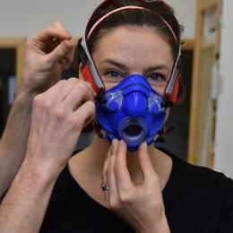 SVT-reportern Malin Gotlin får hjälp att få på ansiktsmasken inför fystestet.