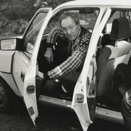 Svartvit bild på Bertil i förarsätet med en pojke i baksätet.