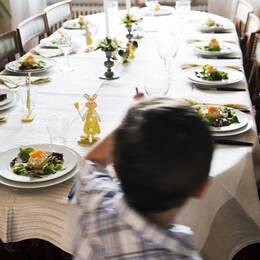 Stort bord med påskdukning och en pojke i förgrunden.