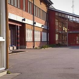 Exteriör bild på Vivallaskolan med asfaltsplan framför.
