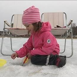 Flicka sitter och pimplar på is i Mårdsjön