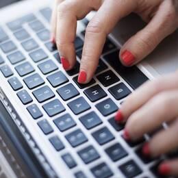 Händer som knappar på ett tangentbord till en dator.