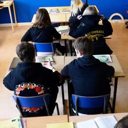 elever sitter vid bänkar i klassrum, sedda baikfrån