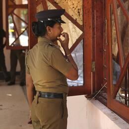 Poliskvinna i Sri Lanka tittar in i en av kyrkorna som attackerades i terrordåden.