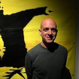 Steve Lazarides framför ett konstverk av Banksy.