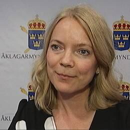 Åklagaren Anna Asklöf framför en vägg med Åklagarmyndighetens logotyp.