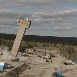 högt torn som är på väg att falla omkull på ett gruvområde i skogen