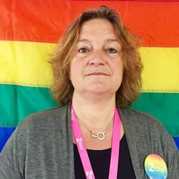Helena Andersson Ssiamanis framför en stor pride-flagga.