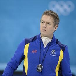 en man i sportjacka med olympiska logotypen