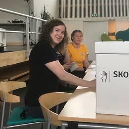 Tre personer som sitter och tar emot röstsedlarna.