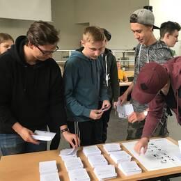 Elever runt ett bord med röstsedlar.
