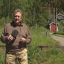 Reporter Kjell Lundström står framför en obevakad järnvägsövergång