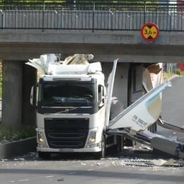 En lastbil sitter fast mitt under järnvägsbron. Sidorna på lastbilen har slagits sönder och ligger utfläkta över asfalten.