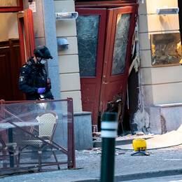 En polis utanför en byggnad som har skadats i en explosion