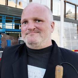 Roger Alexandersson i mörk kavaj och bredrandig grå och vit tröja.