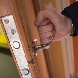 Arrestlokal polisman öppnar dörr till arrest på polisstation