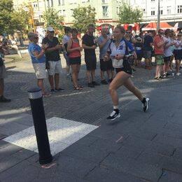 En orienterarer springer på en gata i Norrköping medan folk står och klappar i händerna.