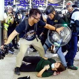 Kvinnlig demonstrant ligger på golvet medan polis och demonstranter bråkar.