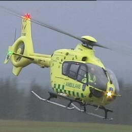 en ambulanshelikopter som flyger nära marken