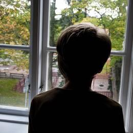 En anonym pojke tittar ut genom ett fönster.