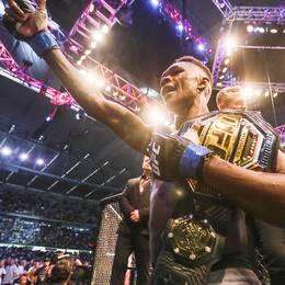 Nye UFC-mästaren Israel Adesanya håller upp sitt bälte.