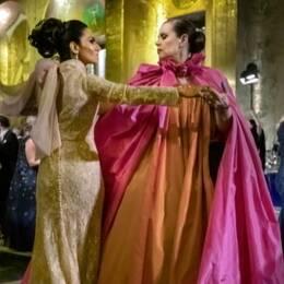 Två kvinnor i långa, uppseendeväckande, klänningar.