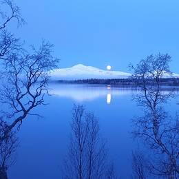 fullmåne över snötäckt fjäll, några träd och blank sjö i förgrund