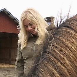 Blond kvinna med en brun häst i en hage