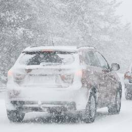 En bilkö i kraftigt snöfall.
