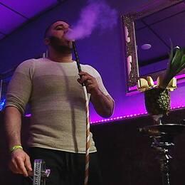 En man som röker vattenpipa.