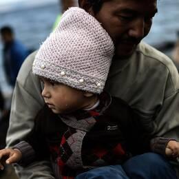 En afghansk flykting anländer till den greksika ön LEsbos med sitt barn i famnen.