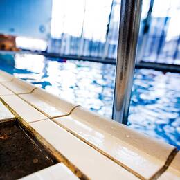 Närbild på stege ner i bassäng i simhall.