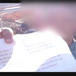 En väktare visar upp en papperslappen och en bild från ESC-området i Kungsträdgården.