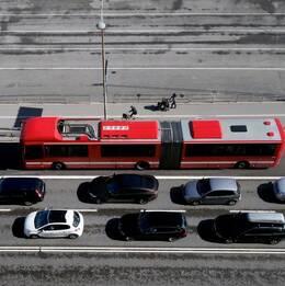 Röd SL-buss åker förbi bilkö.