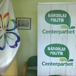 Centerpartiet logotyp och en flagga med partiets klöver i regnbågsfärger