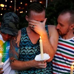 Tre män som deltar i ljusvakan i Orlando gråter tillsammans.