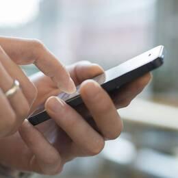 Två händer håller en mobiltelefon