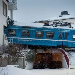 Tågvagn som är halvvägs in i bostadshus