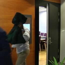 Den åtalade gothia cup-ledaren håller upp en jacka framför sitt ansikte