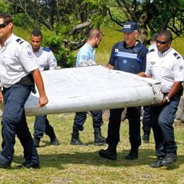 Fransk polis på ön Réunion i Indiska oceanen bär den upphittade vingklaffen efter att den spolats i land på ön förra sommaren. Arkivbild.